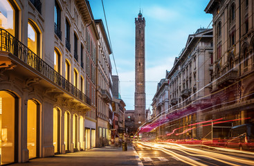Two famous falling Bologna towers Asinelli and Garisenda. Evening view. Bologna, Emilia-Romagna, Italy. Long exposure, time lapse.