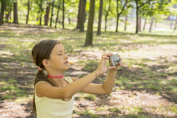 Little girl child of 8 years looking at camera sitting on green lawn in city park. girl 8 years in the park taking pictures of nature