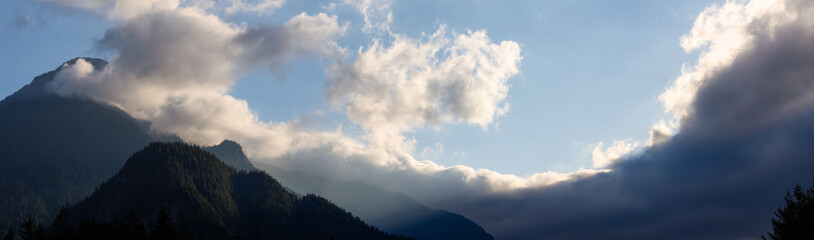 Panoramic view of the striking cloudy sky over the Canadian Mountain Landscape during a vibrant sunset. Taken in Hope, BC, Canada.