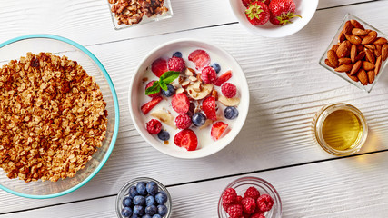 Cereal muesli and sliced bananas, strawberries, blueberries, raspberries, almonds and walnuts with milk in white ceramic bowl on white table. Top view.
