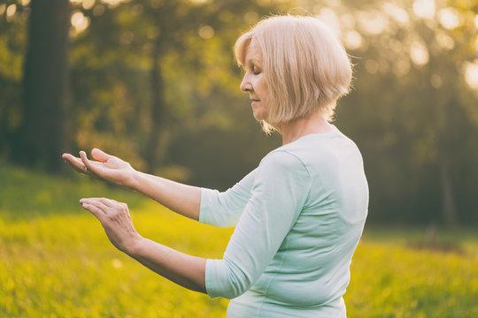 Senior woman enjoys  exercise Tai Chi in the nature.