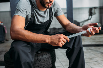 cropped view of professional mechanic holding wrench and sitting in auto repair shop