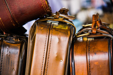 Wallpaper background of classic vintage brown leather travel bags. No people.