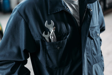 cropped view of workman in overalls with wrenches in pocket Wall mural