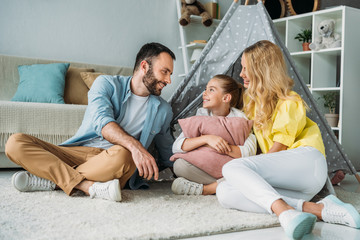 happy young family sitting on floor with teepee