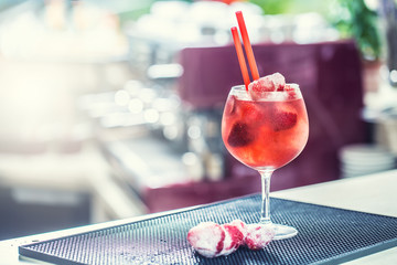Strawberry lemonade or alcoholic cocktail with ice syrup soda and mint leaves on bar table