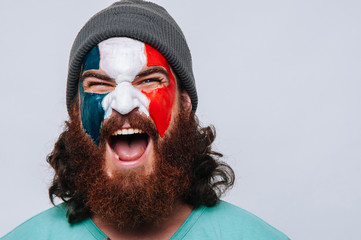 Face of young happy bearded man painted with flag of France. Football or soccer team fan, sport event, faceart and patriotism concept. Studio shot at gray background, copy space