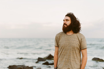 Happy bearded man with long curly hair relaxing outdoor near the sea