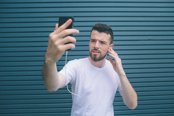 A picture of concentrated man looking at phone he has in hands. Guy is listening to music and posing. He is taking selfie. He looks cool. Isolated on striped and blue background.