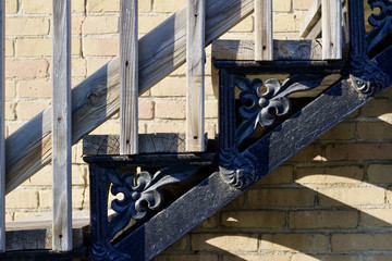 Close up view of an urban fire escape staircase along a tan color brick wall casting shadows in late day sun