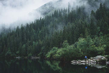 Foggy and mystic mountain forrest with a reflection on the water and person standing in front in Morskie Oko, High Tatras, Zakopane, Poland