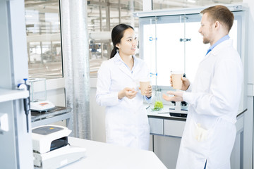 Waist up portrait of two modern young scientists wearing lab coats  chatting while taking break from working in medical laboratory