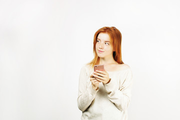Young beautiful woman with long natural red hair, thinking facial expression and pose holding mobile cell phone. Attractive thoughtful hipster female with smartphone in hands. Background, copy space.