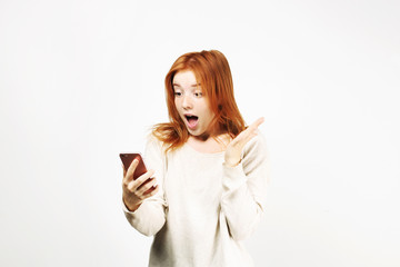 Surprised natural redhead woman with open mouth wearing white oversized loose shirt staring at cell phone screen. amazed hipster ginger female w/ smartphone. Isolated background, copy space, portrait.