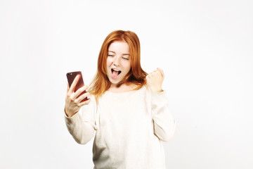 Lucky beautiful young happy woman with natural long red hair celebrating her win, screaming and laughing, looking at her smartphone screen. Attractive female in winning pose. Copy space background.