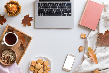 Top view and flat lay of autumn composition background. Laptop, cup of hot tea, book, autumn leaves and flowers, cinnamon cookies on white background.