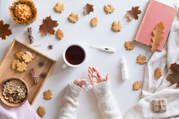 Top view and flat lay of autumn background with cold concept. Woman hands holding thermometer and pills, cup of hot tea, book, autumn leaves and flowers, cinnamon cookies on white background.