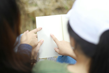 Women are watching the book together.