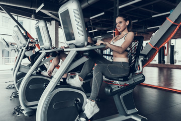 Young Woman in Sportswear on Exercise Bike in Gym.