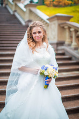 Portrait of delightful bride in white dress and bouquet of flowers, on background of stone staircase in autumn