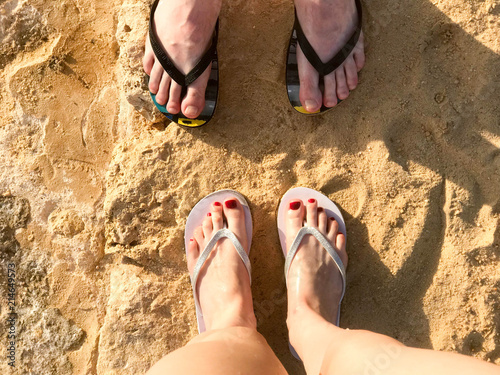 600d87659 Two pairs of male and female legs with a manicure in slippers
