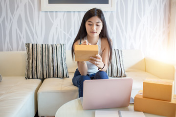 Asian woman is checking the shipping box. And write the address of the recipient. To order online On the Internet of the buyer.