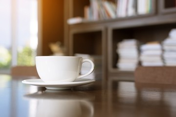 cup coffee on table in cafe. background style library book shelf Morning sunlight.
