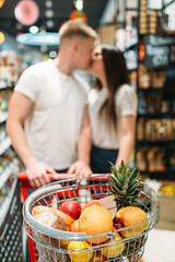 Cart with products, couple kissing in supermarket