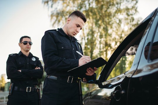 Male police officers check vehicle on the road