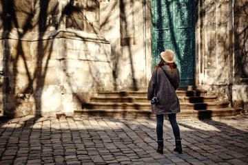 happy and stylish pretty hipster woman holding film photo camera on background of old building  in european city