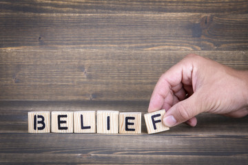 Belief. Wooden letters on the office desk, informative and communication background