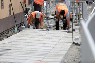 Robotnicy układają kostkę na chodniku w mieście.