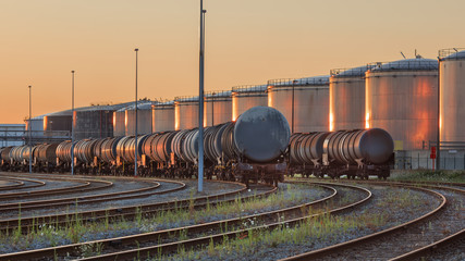 Trains with silos of a petrocemical production plant on the background lit by late afternoon sunlight, Port of Antwerp, Belgium. Wall mural