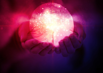 Magic glowing ball with a flash of light in women's hands on an abstract dark background.