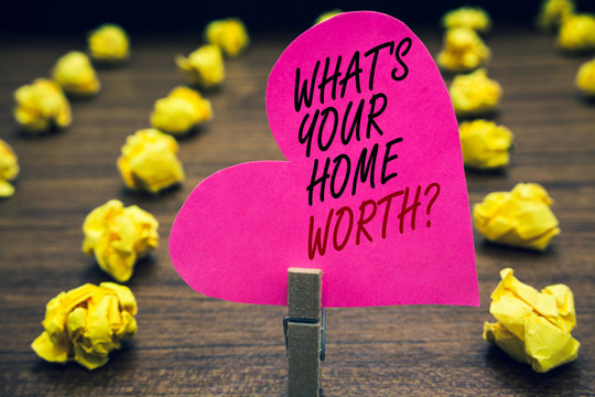 Conceptual hand writing showing What s is Your Home Worth question. Business photo text Value of a house Property Cost Price Rate Paperclip hold pink written heart woody floor with yellow lobs.