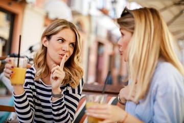 Two women gossiping in a cafe