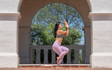 Athletic young woman practicing yoga outdoors, doing Eagle Pose side view