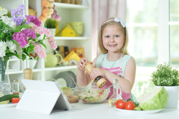 Cute little girl spicing  salad on kitchen table