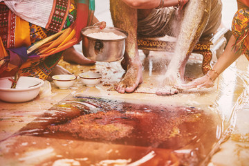 Family members pasting the turmeric powder (haldi) oil mixed with milk on groom's feet and body
