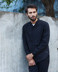 Youth Men's Fashion. A young male hipster with a beard posing on a summer evening outdoors in a fashionable outfit against a gray concrete wall. Black shirt and black trousers. Cover.