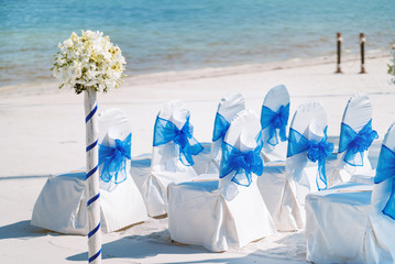 A group of white spandex chairs cover with blue organza sash for beach wedding venue setup