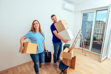 Cheerful Couple Standing In Living Room With Cardboard Boxes. Young family moving in a new apartment concept.