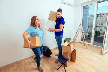 Image of young man and woman with cardboard box. Young family moving in a new apartment concept.