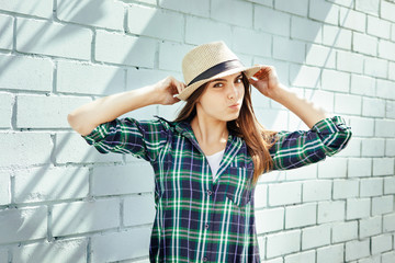 Happy young woman in hat and plaid shirt make faces, near blue brick wall