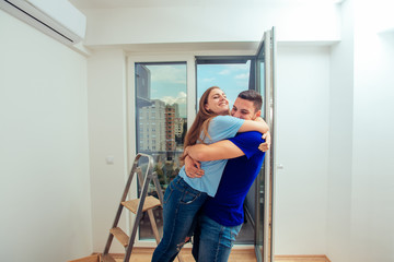 Happy family couple embracing in a new house. Young family moving in a new apartment concept.