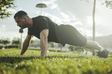 Close up of young attractive man exercising plank outdoors. Side view.