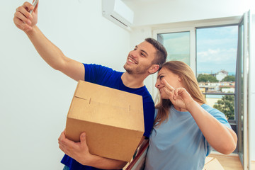 Lovely couple moving into a new house while taking selfie. Young family moving in a new apartment concept.