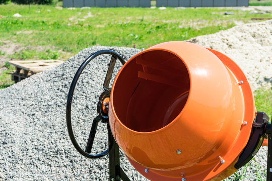 Photo concrete mixer installed on the construction site next to a pile of sand and gravel.