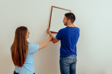 A young married couple decorates their new home. Home decoration and renovation concept.