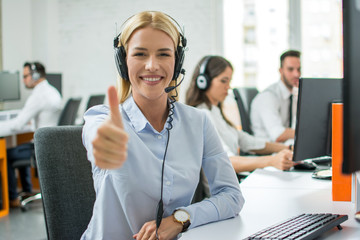 Smiling customer support agent woman showing thumb up in call centre